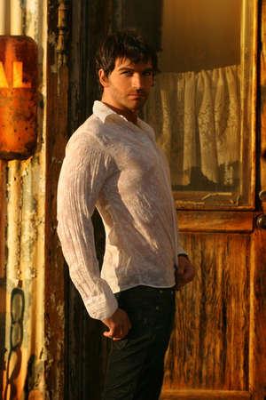 グランジ金属背景に対して暖かい日差しで若い男性モデル