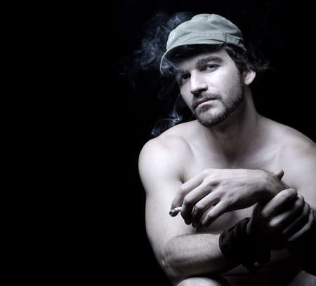 edgy: Sexy studio portrait of a young shirtless muscular military man smoking