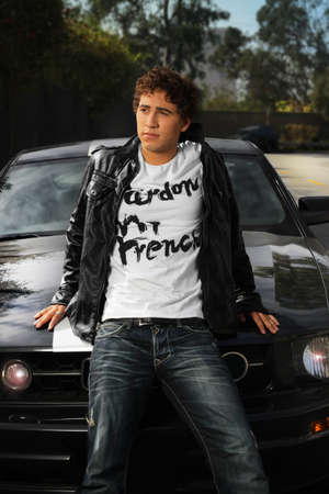 Outdoor portrait of a young trendy man standing against sports car photo