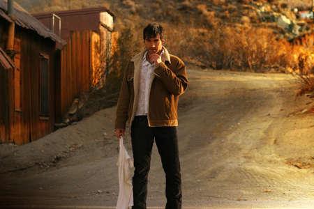 Sexy ruige man staande in het midden van een landelijke weg Stockfoto
