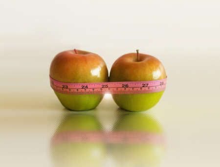 Pair of apples next to each other wrapped in tape measure