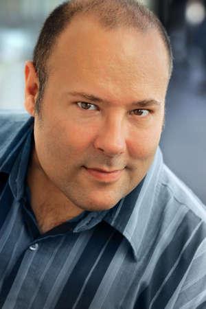 Ritratto del primo piano di un bell'uomo in camicia blu