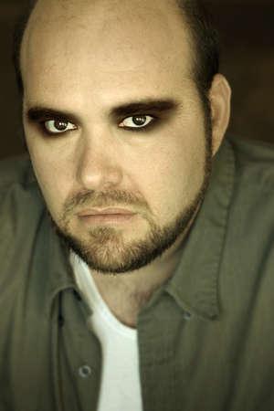 Crazy looking intense portrait of mature man in eye makeup photo