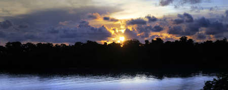 a beautiful island morning sunrise with a sky full of tropical clouds and reflective water in foreground Stock Photo - 7710579