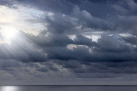 Ominous clouds above the ocean with rays of light peaking through photo