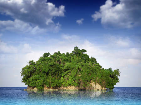 Small island in tropical waters with bright blue sky and clouds above