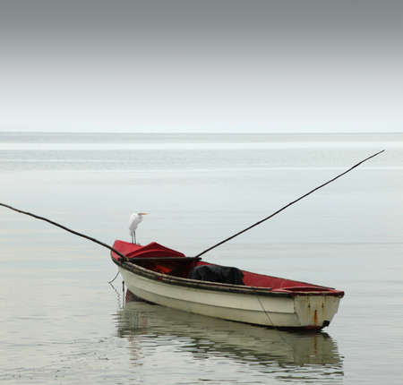 A lonely rowboat on calm seas against moody grey sky photo