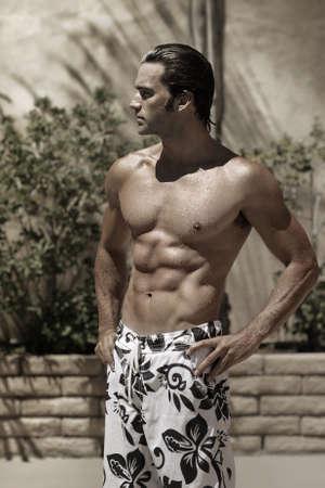 nudo maschile: Stylized portrait of a beautiful muscular wet male model outdoors in swim trunks