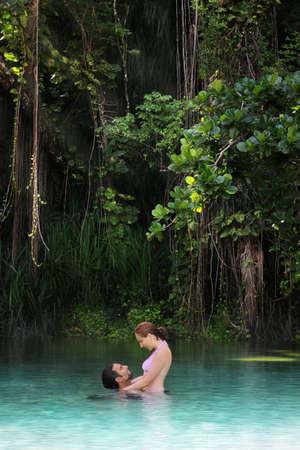 couple enlac�: Jeune couple heureux, embrassant dans un d�cor de paradis tropical isol�  Banque d'images