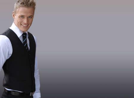 traje: Atractivo empresario joven sonriente contra un fondo neutro con gran cantidad de espacio de copia