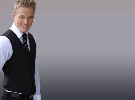 Attractive smiling young businessman against neutral background with lots of copy space photo
