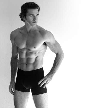 beau jeune homme: Portrait d'un jeune homme torse nu sexy en lingerie sur fond neutre, avec beaucoup d'espace copie