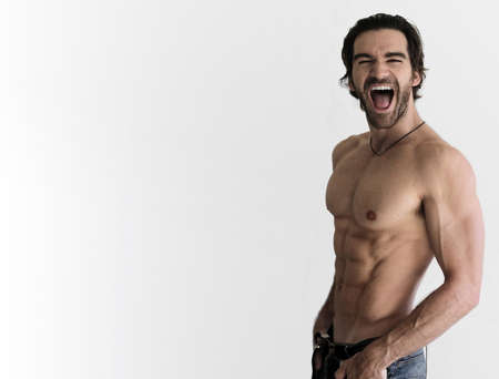 torso only: Sexy shirtless guy laughing against neautral background with lots of copy space Stock Photo