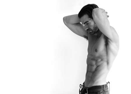 torso only: Black and white portrait of a sexy young shirtless man against white background with lots of copy space Stock Photo