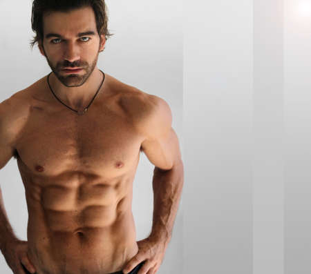 Sexy athletic shirtless man against neutral background photo