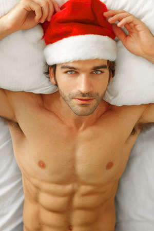christmas costume: Sexy shirtless male model laying back in bed wearing Santa cap