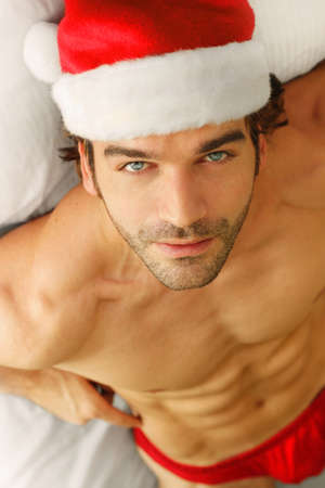 christmas costume: Good looking shirtless young man in Santa Claus hat and briefs in bed