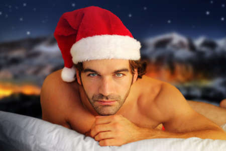 christmas costume: Sensual portrait of a young shirtless male model laying on pillow against fantasy winter background Stock Photo