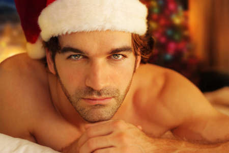 Young man bathed in warm light from fireplace wearing Santa cap photo