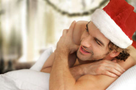 christmas costume: Cute young man in Santa cap laughing and smiling