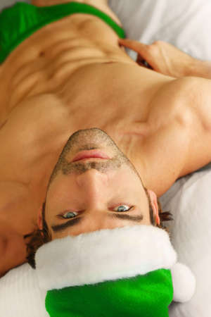 christmas costume: Young sexy male model in green Santa hat and briefs laying in bed