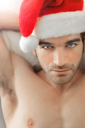 christmas costume: Close up portrait of a sexy attractive man wearing Santa cap in bed