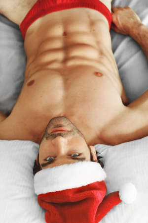 christmas costume: Sexy musuclar man laying shirtless in bed with a Santa cap and red shorts