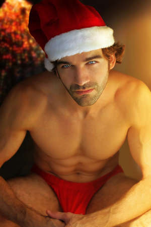 christmas costume: Sexy man in Santa cap next to warm glow of fireplace