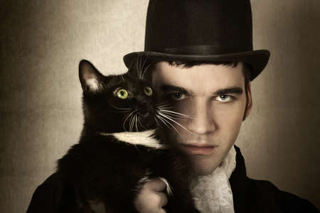 Stylized retro portrait of man in top hat and period clothing with black cat Фото со стока