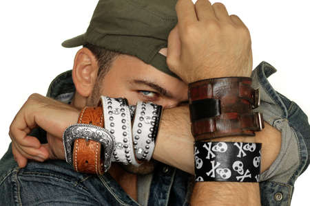 Fashion portrait of male model posing with bracelets backlit against white background