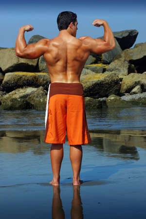Sexy body builder flexing on the beach photo