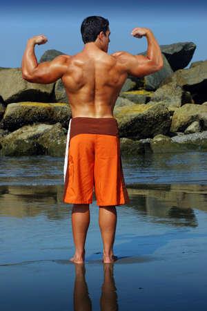 bodybuilding boy: Sexy body builder flexing on the beach Stock Photo