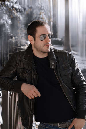 Sexy guy with attitude wearing lether jacket and sunglasses outdoors photo