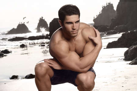 beach hunk: Attractive young body builder posing at the beach Stock Photo