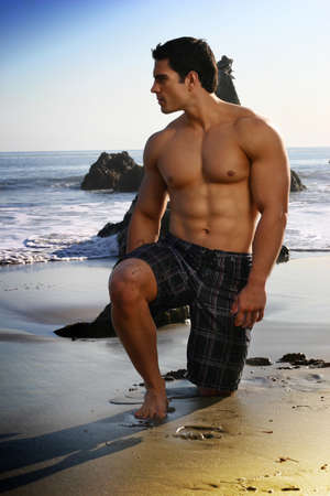 shirtless man: Sexy young fit man on the beach looking out toward the ocean