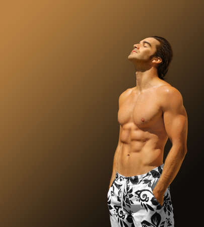 Hansome male fitness model shirtless with hands in pockets looking up with lots of copy space