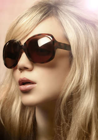 Glamorous fashion portrait of a blond female model wearing cool sunglasses photo