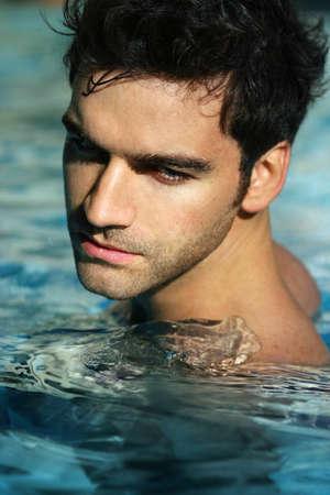 Portrait of a handsome young man in swimming pool photo
