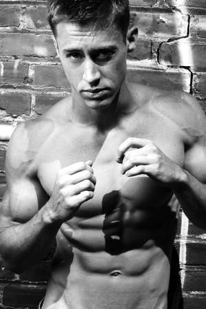 pectorals: Black and white fine art portrait of a young boxer on the street with brick wall background