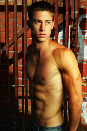pectorals: Sexy shirtless male model in street alley with graffiti Stock Photo