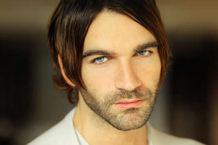 Closeup portrait of a serious good looking young man with long hair