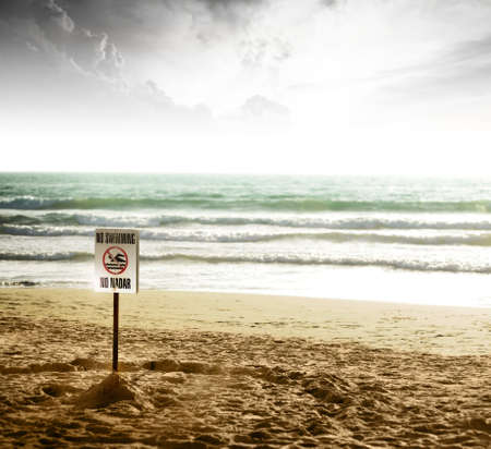 No Swimmin sign on lonely beach with dramatic light and skyscape of clouds Stock Photo - 8581179