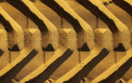 Graphic photo of a wide tire track in golden sand photo