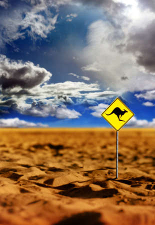 Landscape photo of a kangaroo warning yellow sign in the Australian outback with dramatic sky and red earth Banque d'images