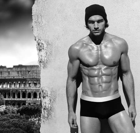 athletic body: Sexy fine art black and white portrait of a very muscular shirtless maile model posing with view of Rome in the background