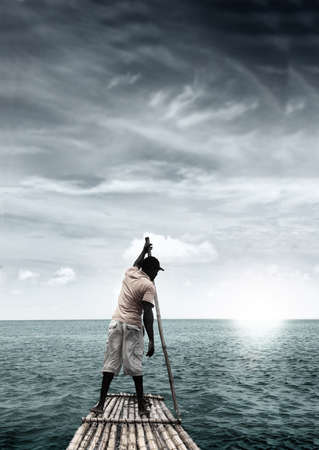 escape: Man on raft in the middle of a tropical ocean paradise with dramatic sky Stock Photo