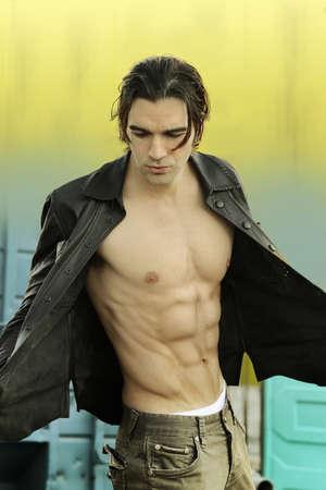 chaqueta de cuero: Retrato de moda de un modelo masculino vanguardista en gran forma, vistiendo chaqueta de cuero con ninguna camisa