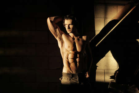 Dark artistic portrait of a sexy muscular shirtless man in industrial garage setting with copy space