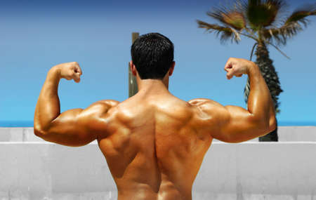 Muscular bodybuilder showing his back on the beach photo