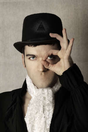 Surreal portrait of a man in top hat making gesture over one eye and having no mouth